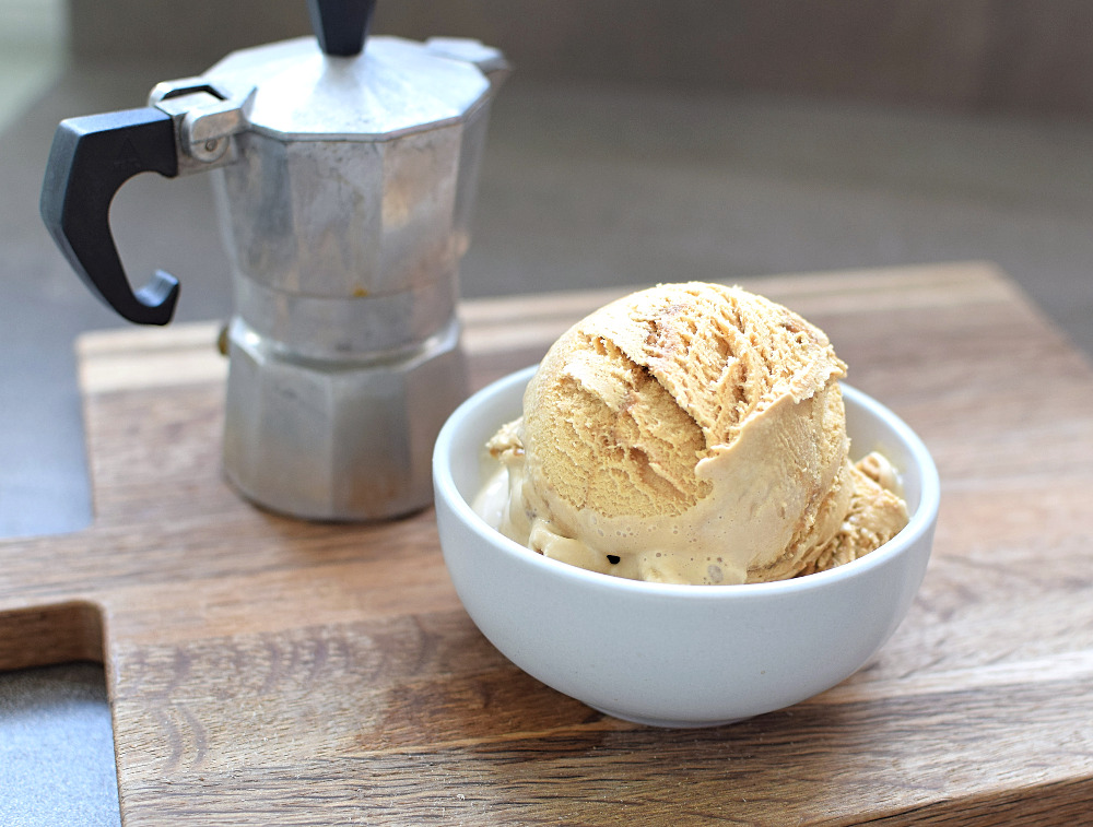 A bowl of coffee ice cream with a jug of coffee next to it.