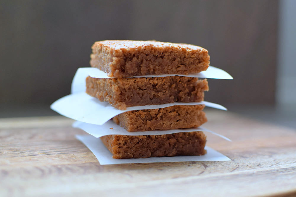 A single stack of blondies with baking papaer in between each one.
