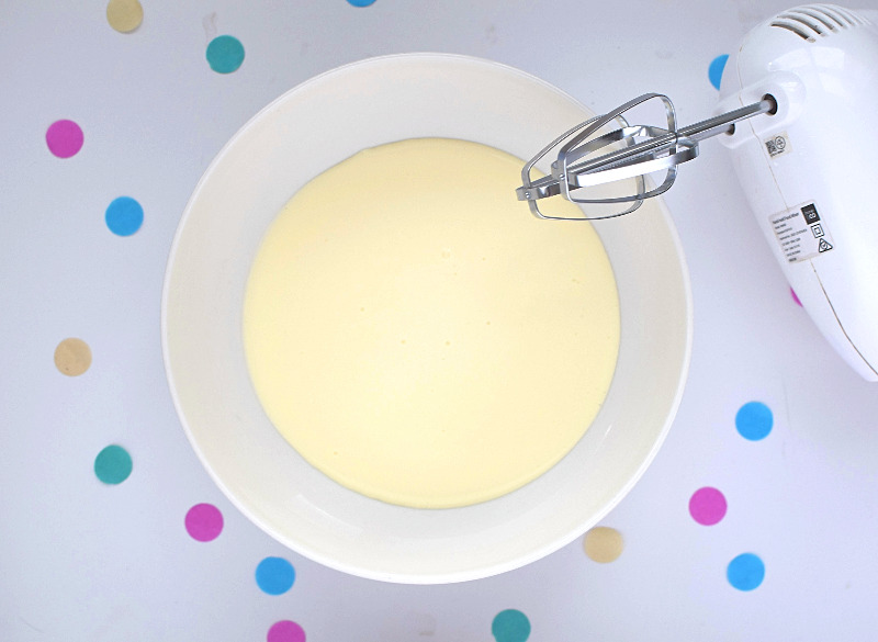 A bowl of cream with a beater next to it