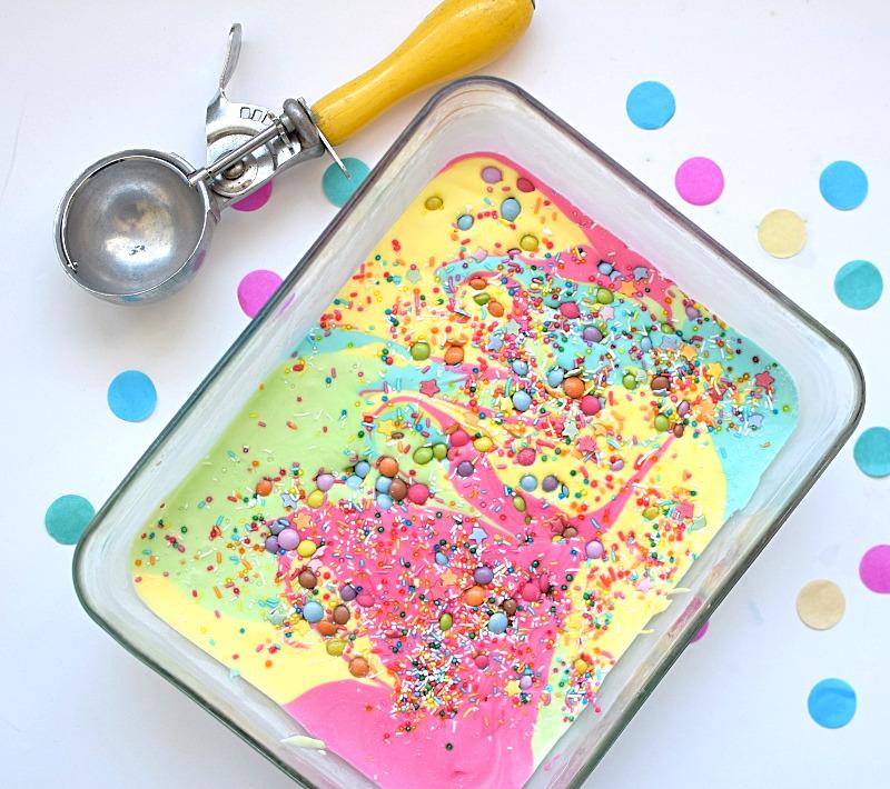 Rainbow ice cream with scoop next to it