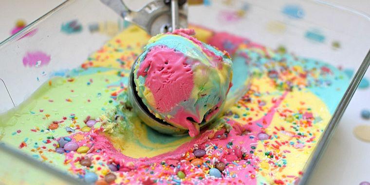 Scooped rainbow ice cream in a dish.
