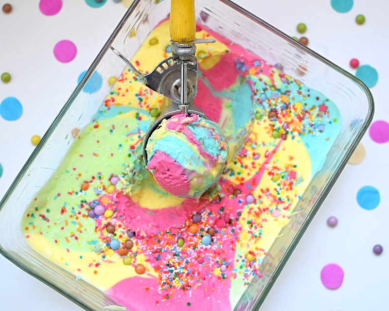 Super colourful rainbow ice cream in a dish with a scoop