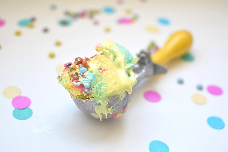 A scoop of rainbow ice cream on bench